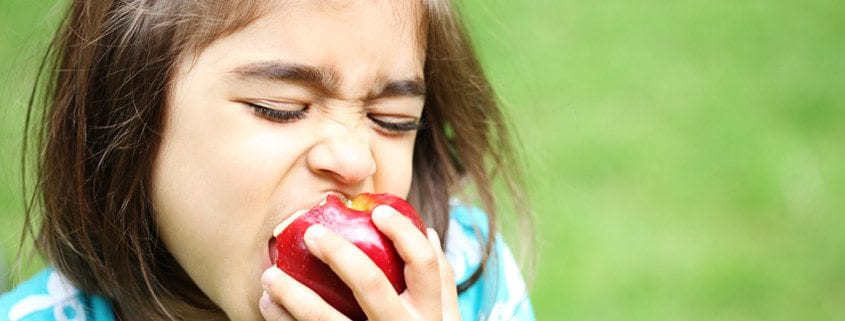 Long girl biting a juicy apple