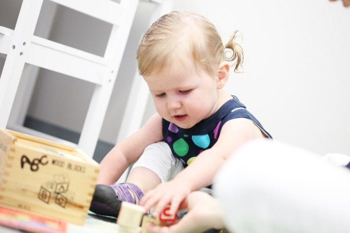 Little girl playing with blocks.